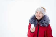 Happy smiling female in red winter jacket holding mobile phone, Stock Photography