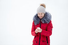Happy smiling female in red winter jacket with mobile phone, out Stock Photography