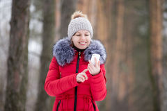 Happy smiling female in red winter jacket with mobile phone, out Stock Image