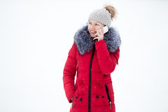 Happy smiling female in red winter jacket talks on mobile phone, Stock Image