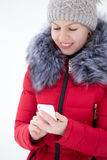 Happy smiling female in red winter jacket texting with mobile ph Royalty Free Stock Photo