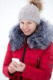 Happy smiling female in red winter jacket texting with mobile ph Royalty Free Stock Image