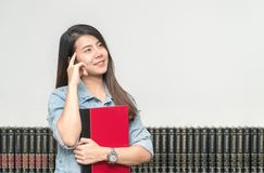Happy smiling female student posing in the university library, s. He is thinking with hand on chin, opportunity learning and education concept concept royalty free stock photo