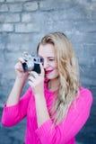 Happy smiling female taking photo on retro vintage hipster camera. Stock Photos