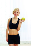 Happy smiling  fit woman holding green apple Stock Photo