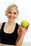 Happy smiling fit woman holding green apple Royalty Free Stock Images