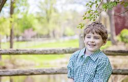 Boy on farm standing under a tree. Happy smiling five year old boy wearing plaid shirt  standing in front of a fence and barn under a tree. Country farm life stock photography