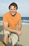 Happy smiling forties man. A colour portrait photo of a happy smiling forties man having fun and relaxing on the beach Stock Photo