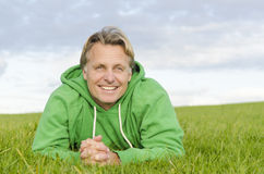 A happy smiling forties man. A color portrait photo of a  happy smiling forties man laying on the grass Stock Photography