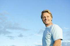 A happy smiling forties man. A color portrait photo of a happy smiling blond haired man in his forties wearing a blue t'shirt against a blue sky backround Stock Photo