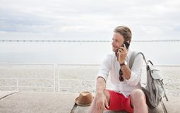Tourist man with backpack talking on a mobile phone by the sea royalty free stock image