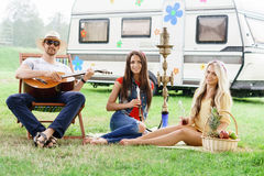 Happy, smiling friends having a picnic outdoors. Royalty Free Stock Images