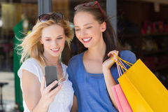 Happy smiling friends looking at smartphone Stock Image