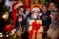 Smiling friends opening magic Christmas gift. Happy smiling friends opening magic Christmas gift Royalty Free Stock Images