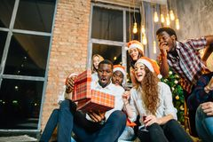 Happy smiling friends opening magic Christmas gift. Happy smiling group of friends opening magic Christmas gift Royalty Free Stock Image