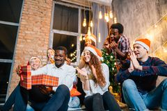 Happy smiling friends opening magic Christmas gift. Happy smiling group of friends opening magic Christmas gift Stock Image
