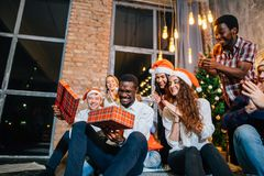 Happy smiling friends opening magic Christmas gift. Happy smiling group of friends opening magic Christmas gift Royalty Free Stock Photos