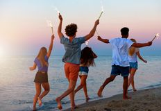 Happy smiling friends running at the beach with sparkling candles stock photo