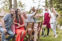 Happy and smiling friends taking photo during grill party in the summer. Photo concept royalty free stock photography