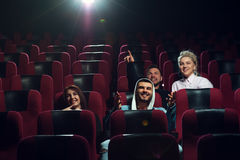 Happy smiling friends watching film in theater Royalty Free Stock Photo