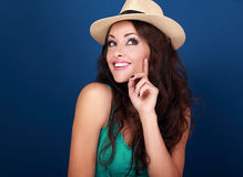 Happy smiling fun makeup woman in summer hat thinking and lookin. G on bright blue background with empty copy space Royalty Free Stock Photo