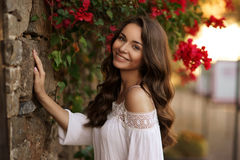 Happy smiling girl against flowers Royalty Free Stock Images