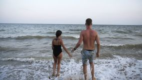 Happy, smiling girl in black swimsuit is taking a hand of her boyfriend from a red tent near the sea and inviting to go. To swim in th sea. Backside footage stock video footage