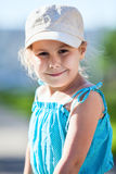 Happy smiling girl in blue dress and cap Royalty Free Stock Images