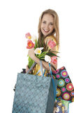 Happy smiling  girl with a bouquet of spring tulips and shopping gift bags. Stock Images