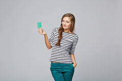 Happy smiling girl in casual clothing, showing blank credit card Royalty Free Stock Photography