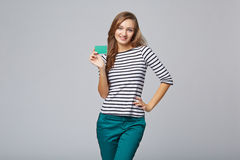 Happy smiling girl in casual clothing, showing blank credit card Stock Photo