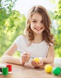 Happy smiling girl coloring easter eggs royalty free stock photos