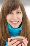 Happy smiling girl with cup of hot drink at winter outdoor. Stock Images