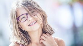 Happy smiling girl with dental braces and glasses. Young cute ca stock image