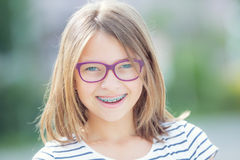 Happy smiling girl with dental braces and glasses. Young cute ca Royalty Free Stock Photo