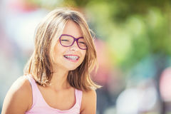 Happy smiling girl with dental braces and glasses. Young cute caucasian blond girl wearing teeth braces and glasses.  Stock Image