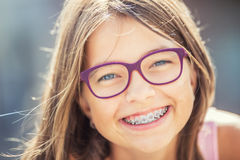 Happy smiling girl with dental braces and glasses. Young cute caucasian blond girl wearing teeth braces and glasses.  Royalty Free Stock Image