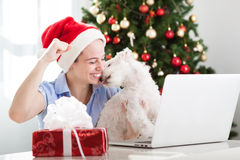 Happy smiling girl and dog using compute and buy presents for Christmas. Holiday Royalty Free Stock Images