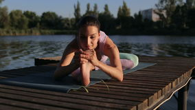 Happy smiling girl doing yoga on a wooden bridge. Happy smiling girl doing yoga on a wooden bridge near the shore of the lake. Sports and healthy lifestyle stock video footage