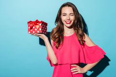 Happy smiling girl in dress holding present box and winking. Portrait of a happy smiling girl in dress holding present box and winking isolated over blue Stock Images
