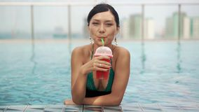 Happy smiling girl drinking cocktail in pool stock footage
