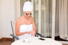 Happy smiling girl early in the morning on the terrace of the hotel to smear her hands with a moisturizing skin cream. Beauty royalty free stock photos