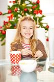 Girl eating cookies at christmas. Happy smiling girl eating cookies at christmas stock images