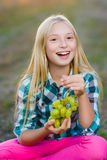 Happy smiling girl eating healthy grapes outdoor Stock Photos