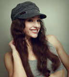 Happy smiling girl in fashion cap. Woman with curly hair Royalty Free Stock Photo
