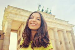 Happy smiling girl in front of Brandenburg Gate, Berlin, Germany. Beautiful young woman travel in Europe. royalty free stock photography