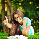 Happy smiling girl in glasses lying in the park near a book and Royalty Free Stock Image