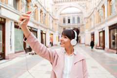 Happy smiling girl in headphones making selfie photo. Cute smiling girl in headphones making selfie photo while standing on a street Stock Photography