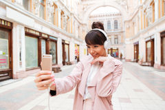 Happy smiling girl in headphones making selfie photo. While standing on a street Stock Photos