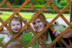Happy smiling girl with her mother looking out between wooden parts of garden house Stock Photo